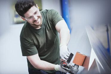 Worker sanding steel in steel factory - CAIF12598