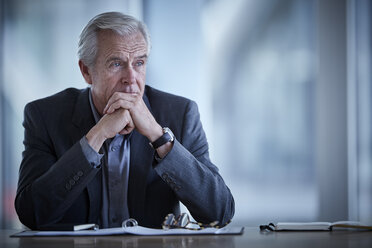 Pensive senior businessman looking away in conference room - CAIF12646