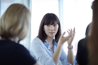 Businesswoman gesturing and talking in meeting - CAIF12670