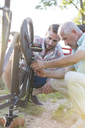 Father and adult son repairing bike chain - CAIF12676