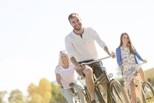 Smiling young man bike riding with women - CAIF12679