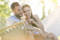 Affectionate young couple smiling in summer hammock - CAIF12685