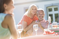 Senior couple smiling and drinking wine on sunny patio - CAIF12694