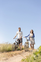 Young couple walking bicycles on dirt road below sunny blue sky - CAIF12697
