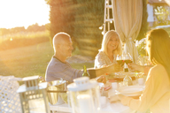 Senior couple an adult daughter toasting wine glasses at sunny patio table - CAIF12706