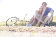 Affectionate young couple hugging near bicycle in rural grass - CAIF12715