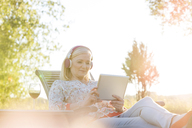 Senior woman with headphones and wine using digital tablet on lounge chair in sunny backyard - CAIF12721