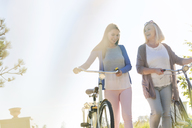 Mother and adult daughter walking bicycles - CAIF12730