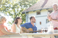 Father opening bottle of rose wine for family at sunny patio table - CAIF12733