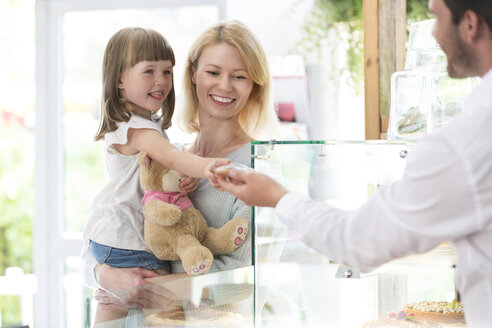 Worker giving girl cookie in bakery - CAIF12760