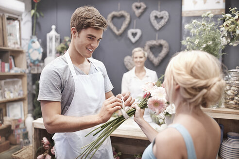 Florist tying flowers for woman in flower shop - CAIF12784