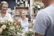 Florists arranging bouquet and talking to customer in flower shop - CAIF12790