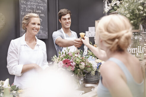 Florist giving woman rose in flower shop - CAIF12793