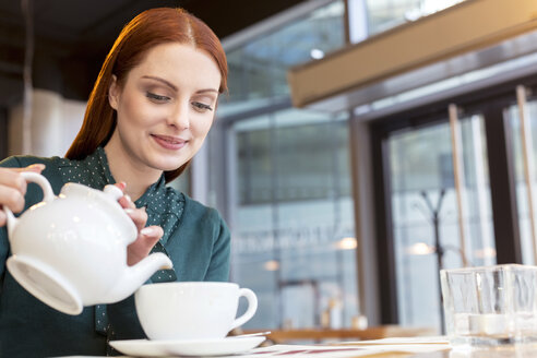 Smiling woman pouring tea in cafe - CAIF12799