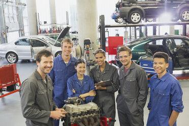 Portrait confident mechanics with car engine in auto repair shop - CAIF12865