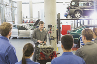 Mechanic explaining car engine to students in auto repair shop - CAIF12877