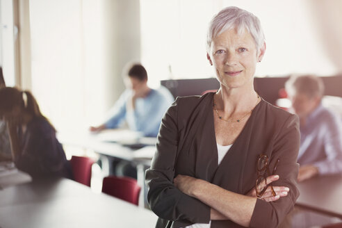 Portrait of confident senior woman in adult education classroom - CAIF12886