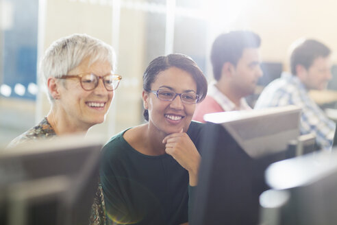 Smiling women at computer in adult education classroom - CAIF12910