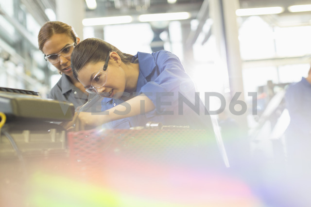 Female mechanics working on engine in auto repair shop - CAIF12937