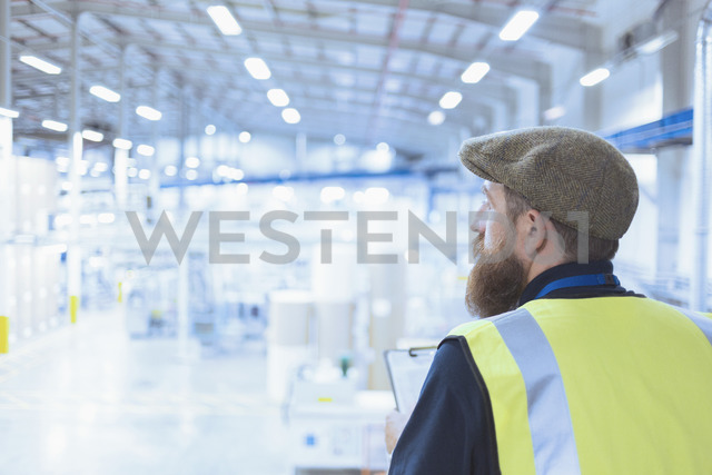 Worker with beard and beret looking out over factory - CAIF12994 - Martin Barraud/Westend61