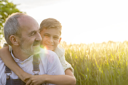 Portrait affectionate grandson hugging grandfather in rural wheat field - CAIF13030
