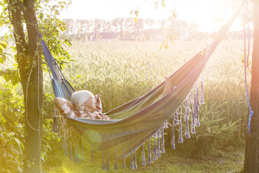 Serene woman napping in hammock next to sunny rural wheat field - CAIF13033
