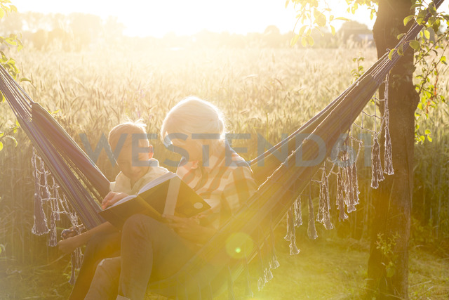 Grandmother and grandson reading book in sunny rural hammock - CAIF13042