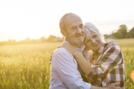 Affectionate serene senior couple hugging in sunny rural wheat field - CAIF13054