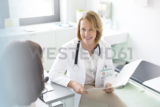 Doctor with medical chart talking with patient in examination room - CAIF13069 - Agnieszka Wozniak/Westend61
