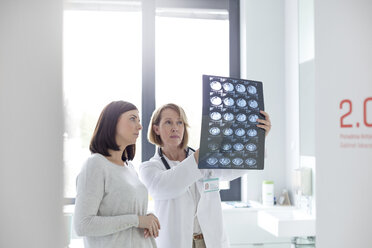 Serious doctor and patient reviewing x-rays in examination room - CAIF13084
