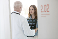Doctor discussing x-rays with serious teenage patient in examination room - CAIF13087