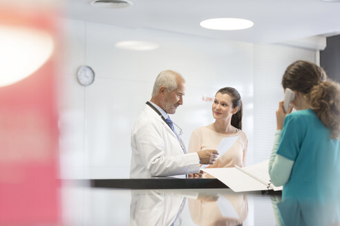 Doctor and patient discussing medical record at nurses station - CAIF13093