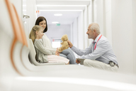 Doctor with teddy bear talking to girl patient in clinic corridor - CAIF13102