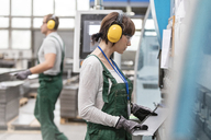 Female worker with ear protectors holding metal part in factory - CAIF13108