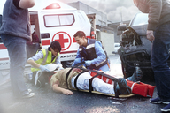 Rescue workers tending to car accident victim in road - CAIF13129