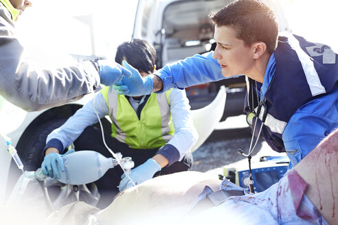 Rescue workers with manual resuscitator over car accident victim in road - CAIF13141