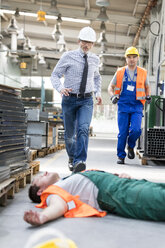 Workers running toward fallen coworker unconscious on factory floor - CAIF13162