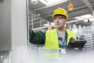 Worker in protective workwear at control panel in factory - CAIF13171
