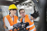 Worker guiding coworker driving forklift in factory - CAIF13177