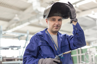 Portrait confident welder with welding torch in factory - CAIF13183
