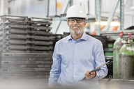Portrait confident engineer with clipboard in factory - CAIF13195