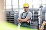 Portrait confident worker with arms crossed in factory - CAIF13198