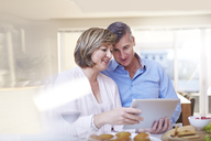 Couple using digital tablet in kitchen - CAIF13213