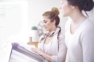 Interior designers browsing fabric swatches in office - CAIF13222