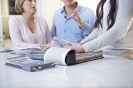 Interior designer discussing swatches with couple in consultation - CAIF13225