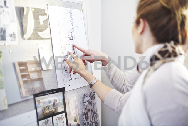 Interior designers discussing blueprints hanging in office - CAIF13231