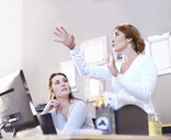 Businesswoman gesturing and explaining to coworker at computer - CAIF13234