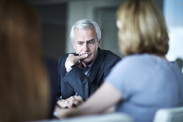 Serious senior businessman looking down in meeting - CAIF13273