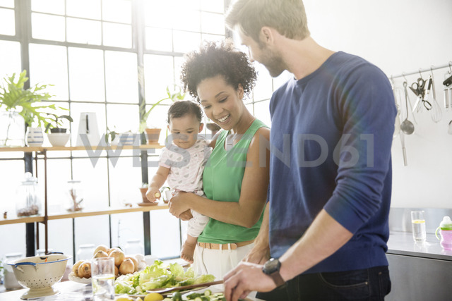 Happy family preparing meal in domestic kitchen - CAIF13291