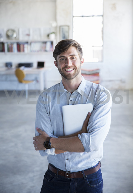 Portrait of young man standing in studio with digital tablet - CAIF13297